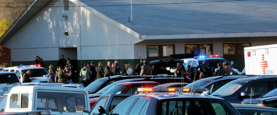 Law enforcement personnel gather at the scene of a shooting at Sparks Middle School in Sparks, Nev. on Monday, Oct. 21, 2013. A student at the school opened fire on campus just before the starting bell Monday, wounding two boys and killing a teacher who was trying to protect other children, Sparks police and the victim's family members said. (AP Photo/The Reno Gazette-Journal, Marilyn Newton) NO SALES; NEVADA APPEAL OUT; SOUTH RENO WEEKLY OUT / The Reno Gazette-Journal