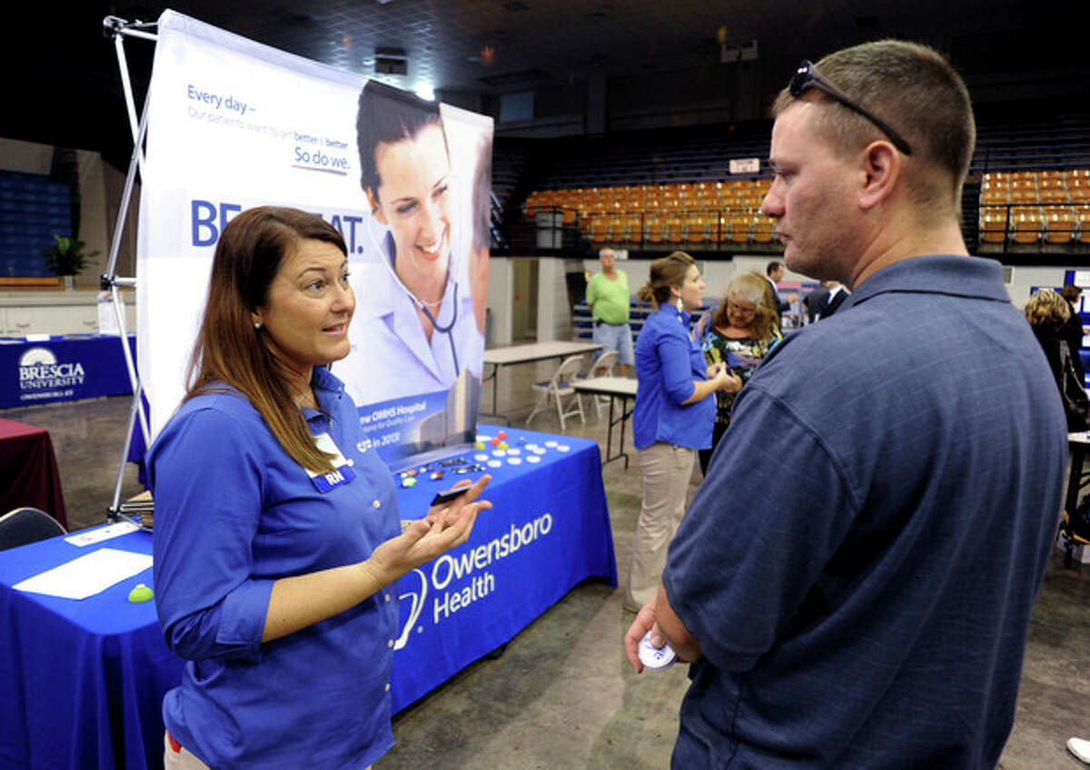 FILE - In this Tuesday, Oct. 1, 2013, file photo, registered nurse Salanda Bowman, left, talks with part-time Kentucky Wesleyan College student Jason Ward, of Whitesville, about job openings at the Owensboro Health Regional Hospital during a Regional Career and Job Fair in the Owensboro Sports Center in Owensboro, Ky. The U.S. economy added just 148,000 jobs in September, suggesting that employers held back on hiring before a 16-day partial government shutdown began Oct. 1. (AP Photo/The Messenger-Inquirer, Gary Emord-Netzley, File)