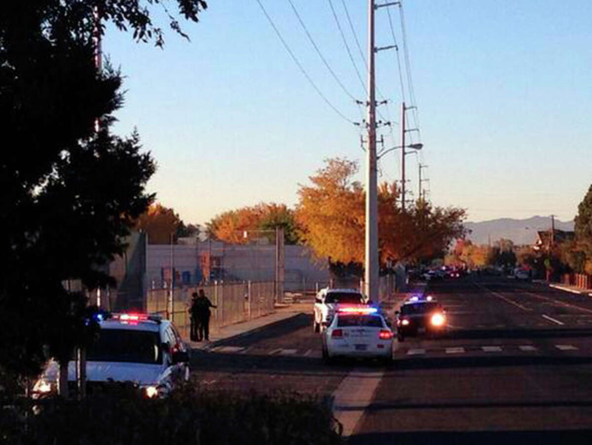In this photo provided by Jerry Davis, police gather near Sparks Middle School after a shooting at the school, Monday, Oct. 21, 2013, in Reno, Nev. A student at the school opened fire on campus, killing a staff member who was trying to protect other children, police said Monday. The suspected gunman is also dead, and authorities say no shots were fired by law enforcement. (AP Photo/Jerry Davis)