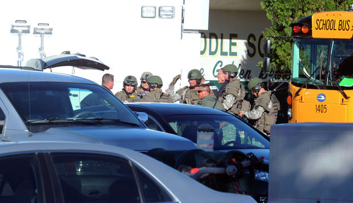 Law enforcement personnel gather at the scene of a shooting at Sparks Middle School in Sparks, Nev. on Monday, Oct. 21, 2013. A student at the school opened fire on campus just before the starting bell Monday, wounding two boys and killing a teacher who was trying to protect other children, Sparks police and the victim's family members said. (AP Photo/The Reno Gazette-Journal, Marilyn Newton) NO SALES; NEVADA APPEAL OUT; SOUTH RENO WEEKLY OUT