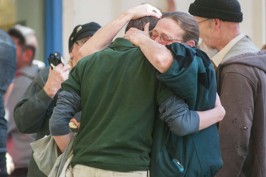 A Sparks Middle School student cries with family members after being released from Agnes Risley Elementary School, where some students were evacuated to after a shooting at Sparks Middle School in Sparks, Nev. on Monday, Oct. 21, 2013 in Sparks, Nev. A student at the Sparks Middle School opened fire on campus, killing a staff member who was trying to protect other children, police said Monday. (AP Photo/Kevin Clifford) / FR159396 AP