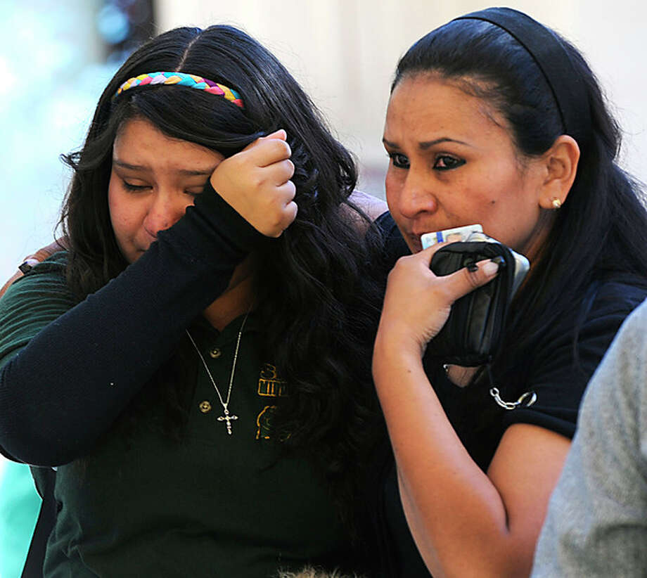 A tearful Michelle Hernandez, left, is led away from Agnes Risley Elementary School following a shooting at Sparks Middle School in Sparks, Nev. on Monday Oct. 21, 2013. A student at the middle school opened fire on campus just before the starting bell Monday, wounding two boys and killing a teacher who was trying to protect other children, Sparks police and the victim's family members said. (AP Photo/The Reno Gazette-Journal, Marilyn Newton) NO SALES; NEVADA APPEAL OUT; SOUTH RENO WEEKLY OUT / The Reno Gazette-Journal