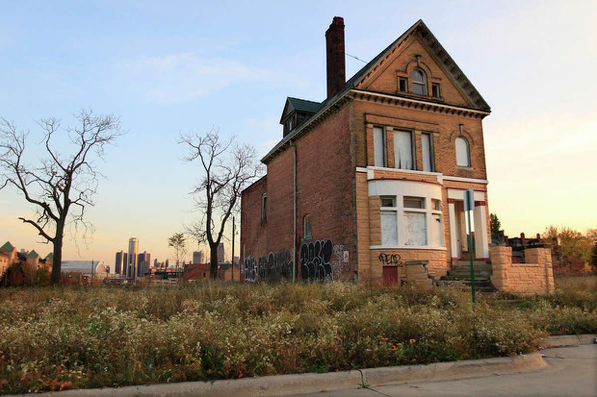 FILE - This Oct. 24, 2012 file photo shows a graffiti-marked abandoned home north of downtown Detroit, in background. Thousands of Detroit streetlights are dark, many more residents have fled. Donors are replacing ambulances that limped around for 200,000 miles. Detroit's bankruptcy case is going to trial, Wednesday, Oct. 22, 2013, and the result will determine whether the city can reshape itself in the largest public bankruptcy filing in U.S. history. (AP Photo/Carlos Osorio, File)