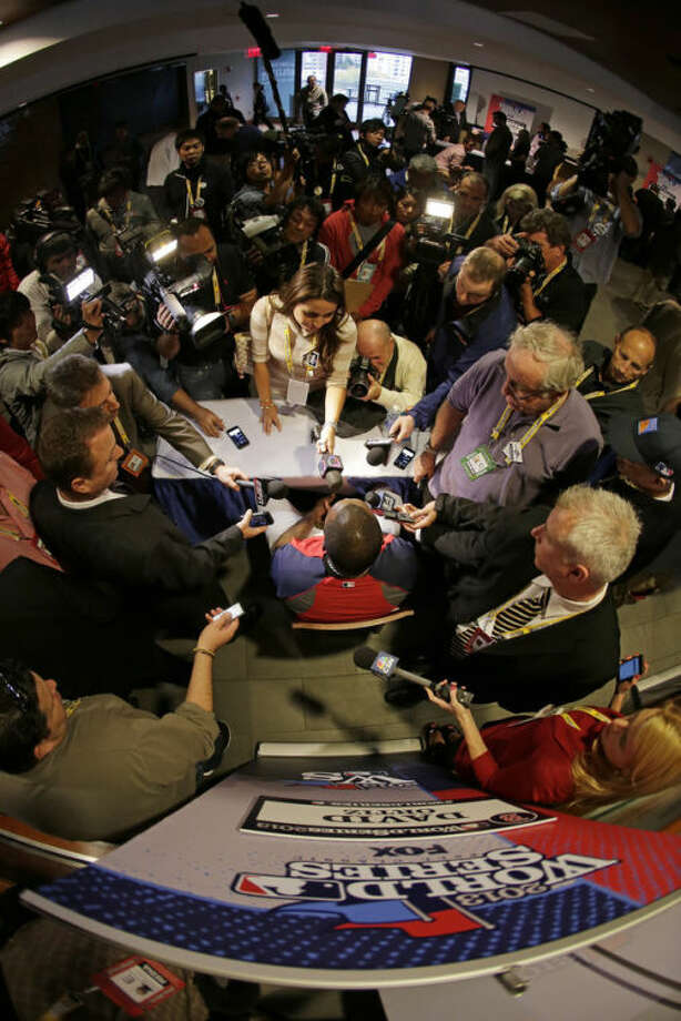 In this image taken with a fisheye lens, Boston Red Sox's David Ortiz, center, answers questions during a media availability Tuesday, Oct. 22, 2013, in Boston. The Red Sox are scheduled to host the St. Louis Cardinals in Game 1 of baseball's World Series on Wednesday. AP Photo/Charlie Riedel)