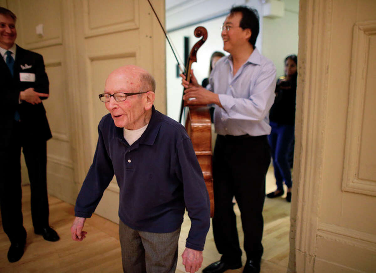 Cellist Yo-Yo Ma, right, follows Holocaust survivor George Horner for a rehearsal at Symphony Hall Tuesday afternoon, Oct. 22, 2013, in Boston. The 90-year-old pianist will make his orchestral debut with Ma Tuesday night, where they will play music composed 70 years ago at the Nazi prison camp where Horner was imprisoned. (AP Photo/Steven Senne)