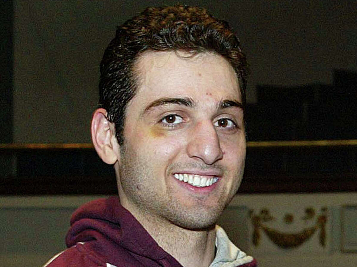 FILE - In this Feb. 17, 2010, file photo, Tamerlan Tsarnaev smiles after accepting the trophy for winning the 2010 New England Golden Gloves Championship in Lowell, Mass. Prosecutors in the case against Boston Marathon bombing suspect Dzhokhar Tsarnaev, Tamerlan's brother, say a man shot to death during questioning by an agent in Florida told investigators that Tamerlan had been involved in a triple homicide (AP Photo/The Lowell Sun, Julia Malakie File) MANDATORY CREDIT