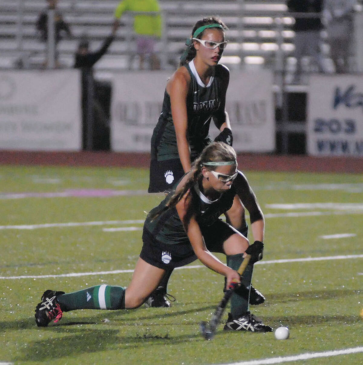 Hour photo/John Nash Norwalk's Greta McConnell, front, gets low to fire off a shot as teammate Sam Bartush looks on during a penalty corner in the second half of Tuesday's FCIAC field hockey game against Trumbull. The Bears and Eagles tied at 1-1.