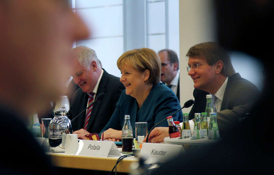German Chancellor Angela Merkel, center, opens coalition talks with representatives of the Social Democrats in Berlin, Germany, Wednesday, Oct. 23, 2013. Merkel on Wednesday launched coalition negotiations with the main opposition Social Democrats, SPD, that are likely to set the stage for weeks of hard bargaining to form a new government. (AP Photo/Michael Sohn) / AP