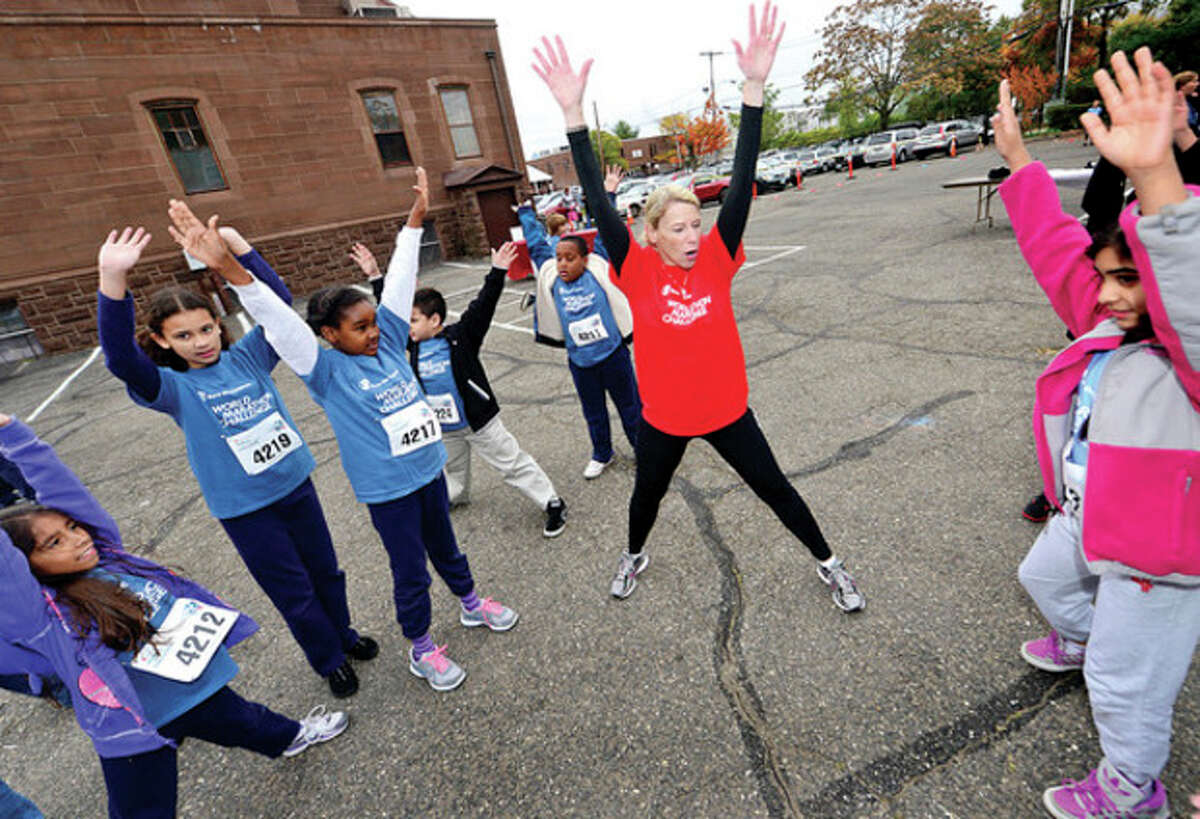 Save the Children CEO Carolyn Miles warms up Side by Side 4th- and 5th-graders as they participate in the World Marathon Challenge, a fundraiser for Save the Children Wednesday.