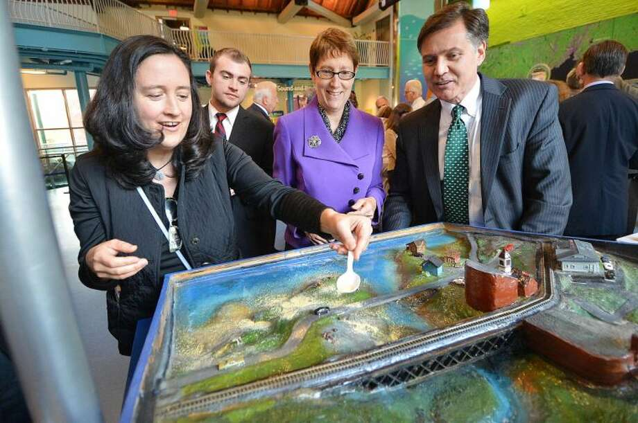 """Hour Photo/Alex von Kleydorff Jennifer Herring, President and CEO Maritime Aquarium and Daniel C. Esty Connissioner, CT Department of Energy and Environmental Protection watch as Bernadette Giblin, Organic Turf Consultant with NOFA places some simulated fertilizer on a display that promotes """" Keep The Sound Healthy"""" during the Grant Award announcement at The Maritime Aquarium for funds to improve the health of Long Island Sound. The projects will be funded through the Long Island Sound Futures Fund."""