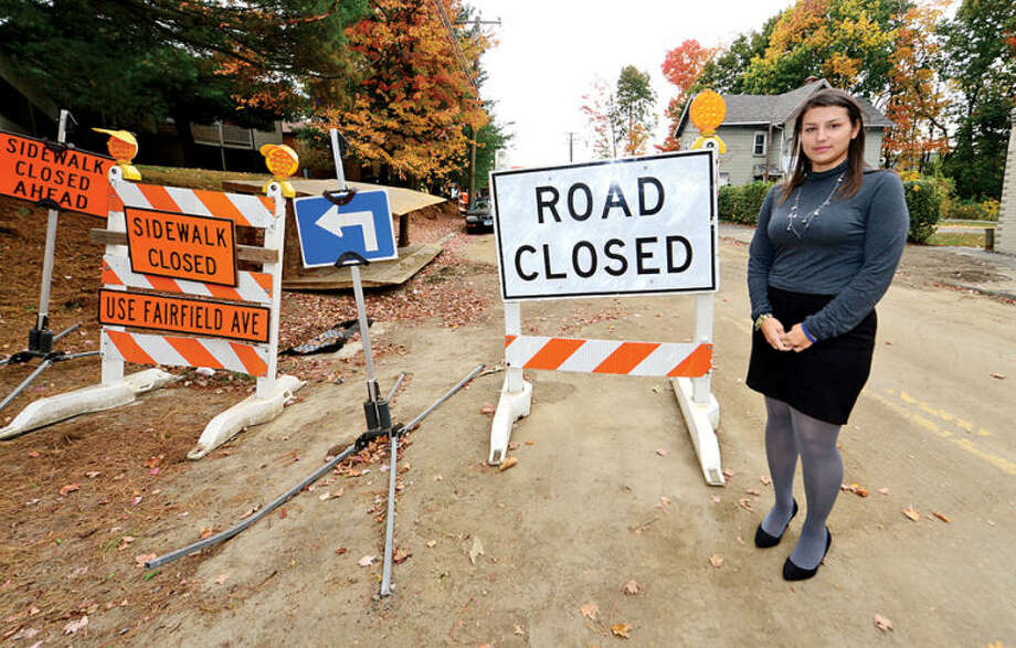 """Hour photo / Erik Trautmann Construction has begun on street repair and sidewalk replacement on Cedar St. in Norwalk. Latino business owners including Nathalia Gonzelez at her bookkeeping business """"Green Books on Cedar Street say they weren't notified by city of roadwork outside their doors."""