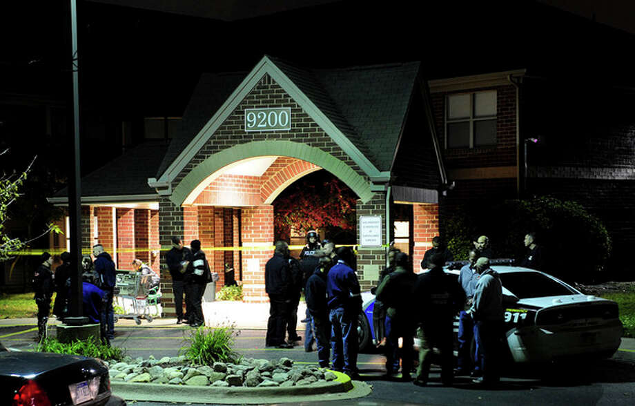 Police swarm the scene after two women were gunned down around 5:45 p.m. Sunday, Oct. 20, 2013 at the Pablo Davis Elder Living Center in Detroit, Mich. A 65-year-old man who lives at the senior center was in custody Sunday after police said he shot and killed two women that he blamed for a breakup with his girlfriend. (AP Photo/The Detroit News Ricardo Thomas)DETROIT FREE PRESS OUT; HUFFINGTON POST OUT / The Detroit News