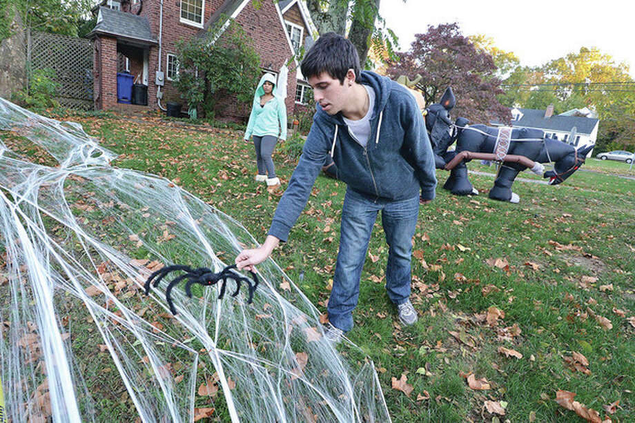 Hour Photo/Alex von Kleydorff Nephew Nick Lepper places a spider on some webbing to add to the decorated front lawn of the Kortekaas house in Norwalk