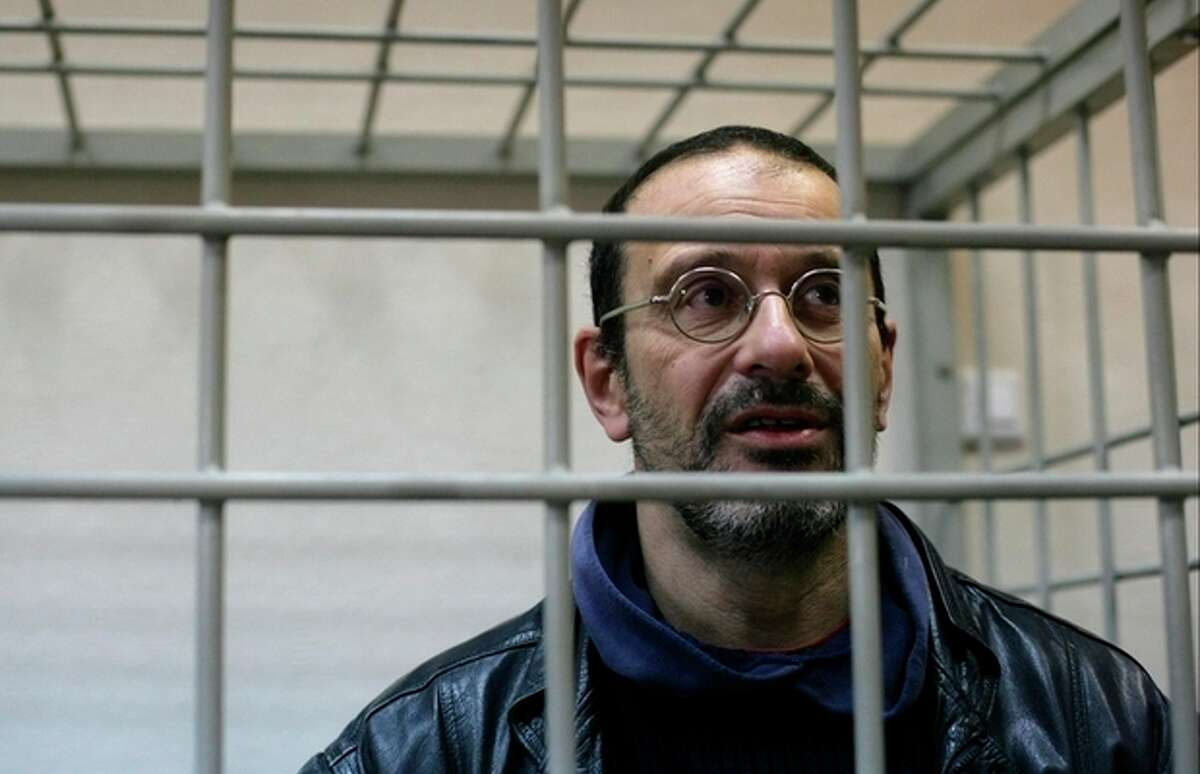 In this photo released by Greenpeace International, activist Dima Litvinov from Sweden looks from a defendants' cage at the district court, in Murmansk, Russia, Wednesday, Oct. 23, 2013. Litvinov is one of the 'Arctic 30' who are in custody charged with piracy, punishable for up to 15 years in jail, after being detained on board the Greenpeace ship Arctic Sunrise, which was seized nearly four weeks ago by Russian security forces after some activists tried to scale an offshore oil platform. (AP Photo/Greenpeace International, Igor Podgorny)