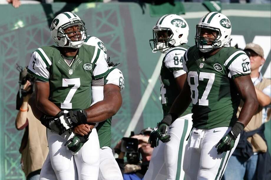 New York Jets quarterback Geno Smith (7) celebrates with teammates after scoring a touchdown during the second half of an NFL football game against the New England Patriots on Sunday, Oct. 20, 2013, in East Rutherford, N.J. (AP Photo/Kathy Willens) / AP