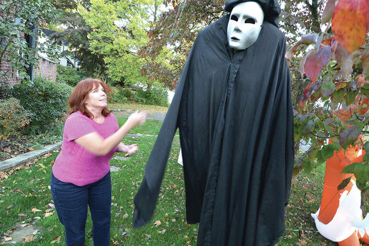 Hour Photo/Alex von Kleydorff Jennifer Kortekaas hoists a ghost into a tree in the front yard of the house in Norwalk. Preparations are underway for their 15th year of decorations for the Halloween season starting with their annual party two weekes before.
