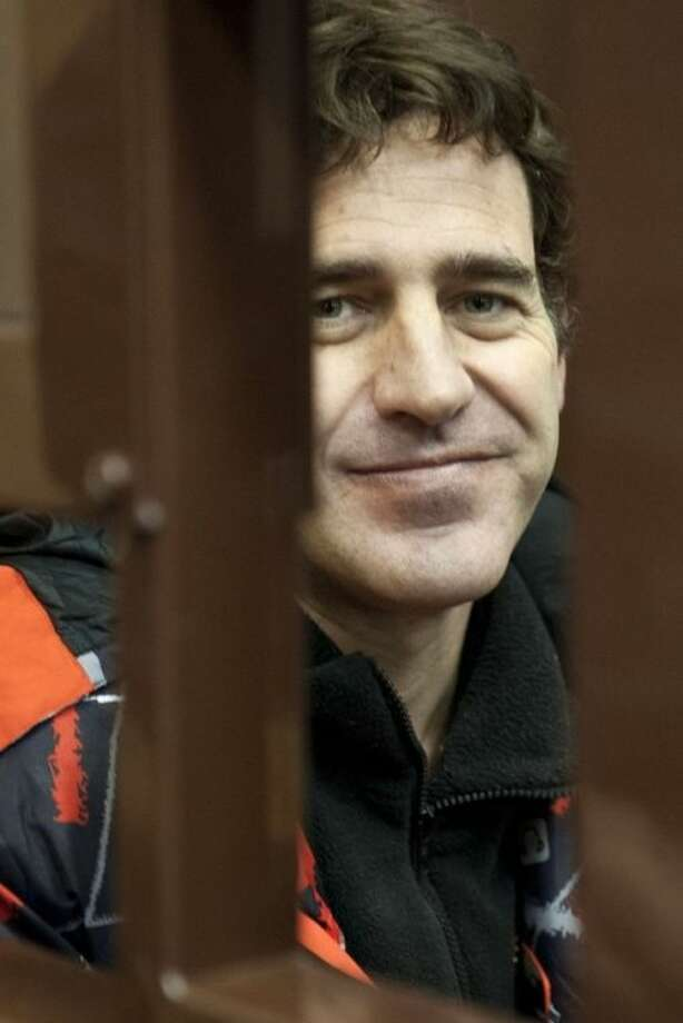 In this photo released by Greenpeace International one of the activists Miguel Hernan Orsi from Argentina sits in a defendants' cage at a Murmansk district court, in Murmansk, Russia, Wednesday, Oct. 23, 2013. Miguel Hernan Orsi is one of the 'Arctic 30' who are in custody charged with piracy, punishable for up to 15 years in jail, after being caught on board the Arctic Sunrise, which was seized four weeks ago by Russian security forces after some activists tried to scale an offshore oil platform. (AP Photo/Greenpeace International, Dmitri Sharomov)