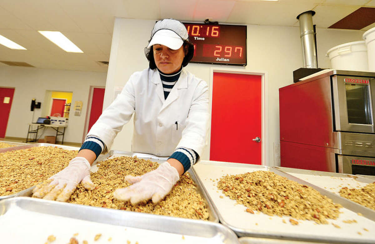 Hour photo / Erik Trautmann Employees at Ola! granola including Mirta Morales manufacture their vanilla almond flavor at the facility in Norwalk.