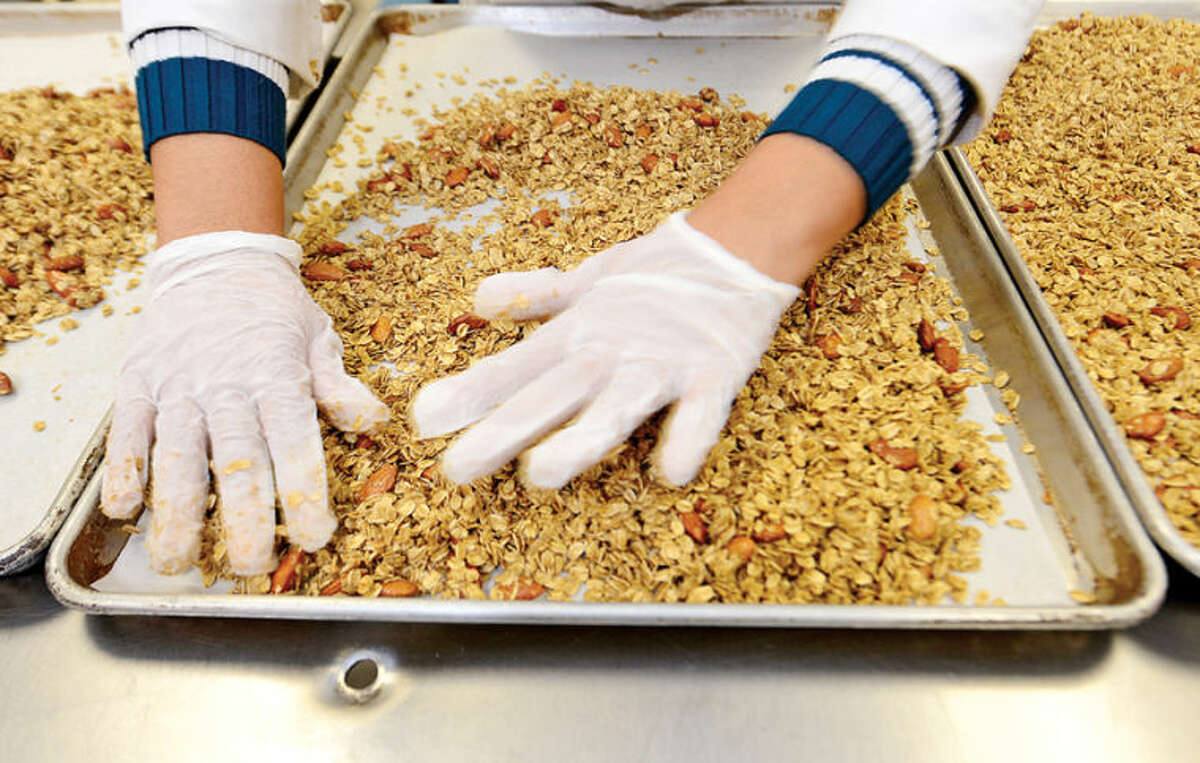 Hour photo / Erik Trautmann Employees at Ola! granola manufacture their vanilla almond flavor at the facility in Norwalk.