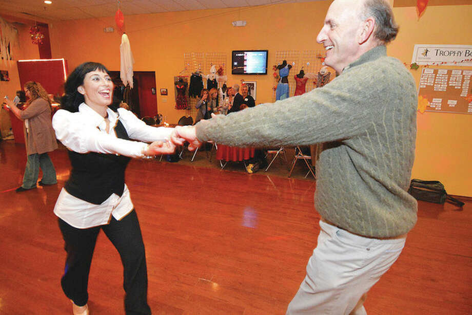 Hour Photo/Alex von KleydorffAbove, Fred Asataire Dance Studio owner Gina Goethche takes Star dancer Peter Tauck for a spin on the dance floor during a reception for the dancers who will compete to benefit Elderhouse. Below, FredAstaire Dance Studio owner Gina Goethche with her pro dancers pose with the Star dancers Peter Tauck, Gina Zangrillo, Cindi Bigelow, Ruthann Walsh and Gus Pappajohn to benefit Elderhouse