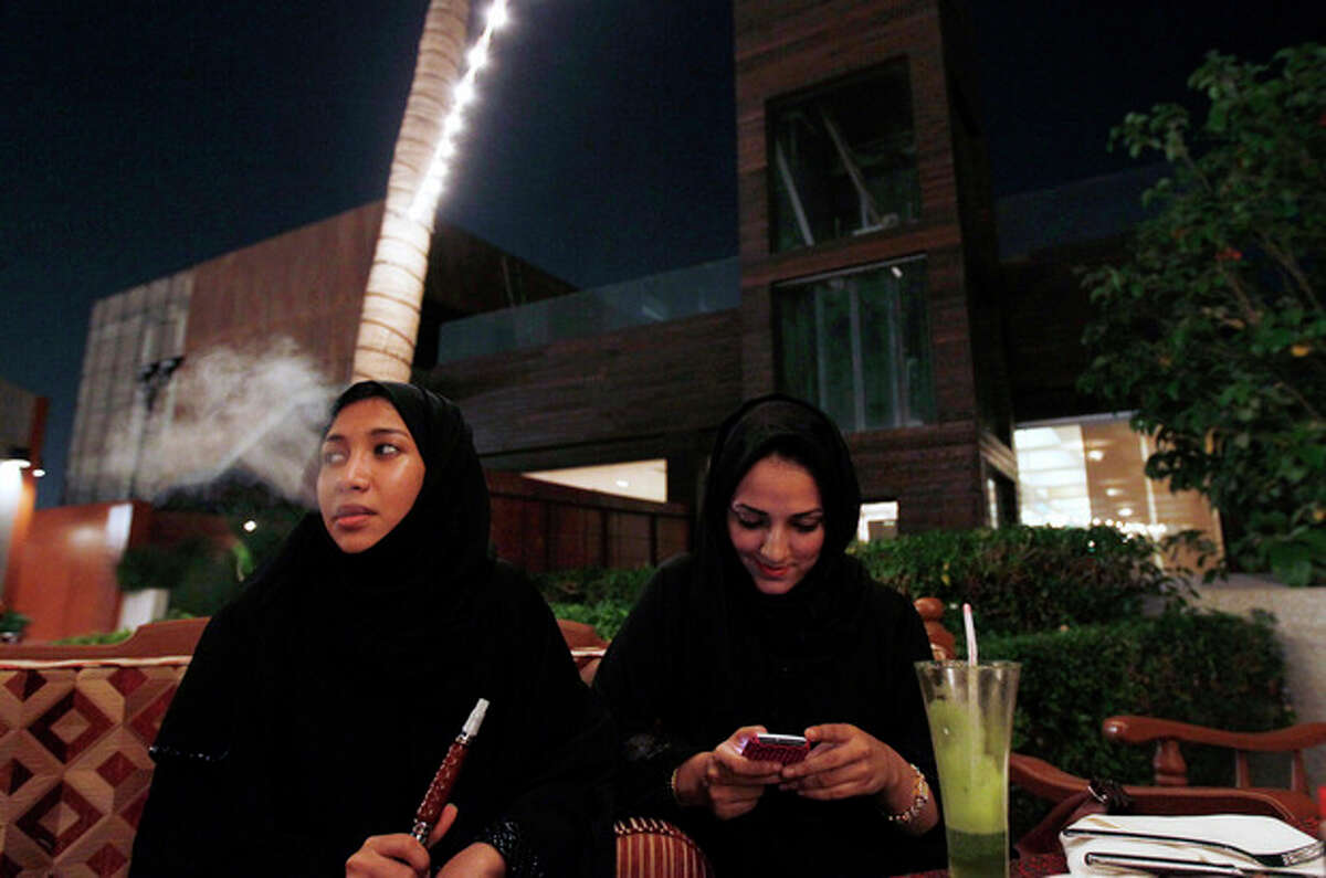 FILE - In this Nov. 11, 2010 file photo, a Saudi woman smokes tobacco from a waterpipe as her friend looks at her cell phone in a coffee shop in Jeddah, Saudi Arabia. It?'s been a little more than two years since the last time women in Saudi Arabia campaigned for the right to drive. Since then, the monarchy has made incremental but key reforms, and activists hope that has readied the nation for greater change as they call for women to get behind the wheel in a new campaign Saturday, Oct. 26, 2013. Ultraconservatives are pushing back with protests, threats and even a cleric?'s warning that driving a car damages a woman?'s ovaries. (AP Photo/Hassan Ammar, File)
