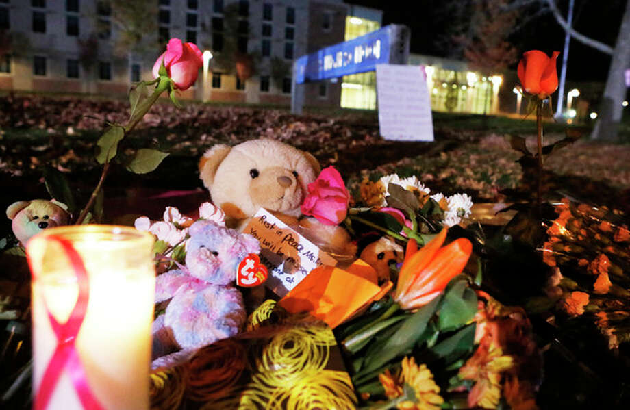 Candles and teddy bears are placed at Danvers High School prior to a candlelight vigil to mourn the death of Colleen Ritzer, a 24-year-old math teacher at Danvers High School on Wednesday, Oct 23, 2013, in Danvers, Mass. Ritzer was found slain in woods behind the high school, and Danvers High School student Philip Chism, 14, who was found walking along a state highway overnight was charged with killing her. (AP Photo/ Bizuayehu Tesfaye) / FR30253 AP
