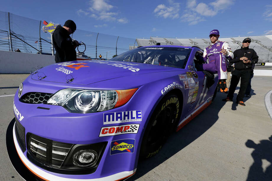 Denny Hamlin climbs out of his car during qualifying for Sunday's NASCAR Sprint Cup series auto race at Martinsville Speedway in Martinsville, Va., Friday, Oct. 25, 2013. Hamlin won the pole. (AP Photo/Steve Helber) / AP