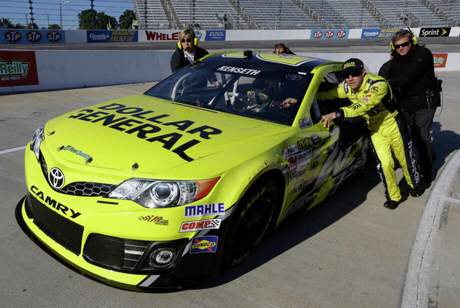 Matt Kenseth helps push his car on pit row during qualifying for Sunday's NASCAR Sprint Cup series auto race at Martinsville Speedway in Martinsville, Va., Friday, Oct. 25, 2013. (AP Photo/Steve Helber) / AP
