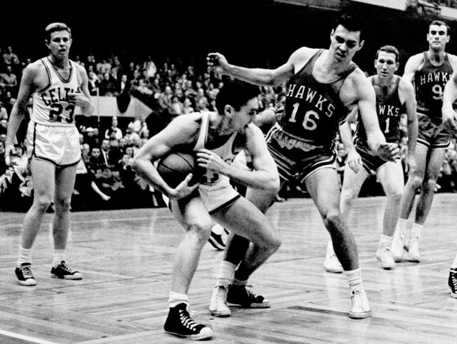FILE - In this March 30, 1958, file photo, Boston Celtics' Bill Sharman holds the ball as St. Louis Hawks' Cliff Hagan (16), defends, during the second half of an NBA Finals basketball game in Boston. Sharman, the Hall of Famer who won NBA titles as a player for the Boston Celtics and a coach for the Los Angeles Lakers, has died. He was 87. Sharman died Friday, Oct. 25, 2013, at his home in Redondo Beach, the Lakers announced. (AP Photo/J. Walter Green, File) / AP