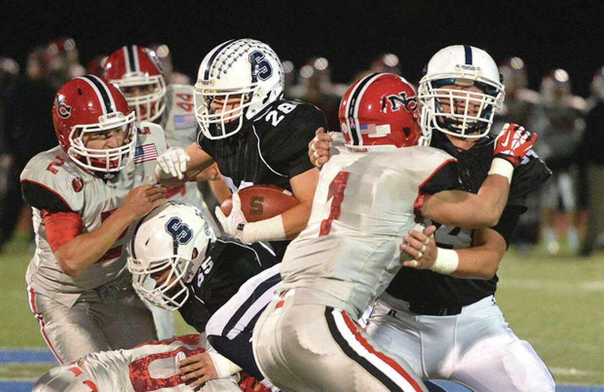 Hour photo/Alex von Kleydorff Jack Greenwald (28) of Staples bulls through the line on the way to a touchdown during Friday night's game against New Canaan. Greenwald's TD was one of the few highlight for the Wreckers, who absorbed a 43-7 beating at the hands of the Rams.