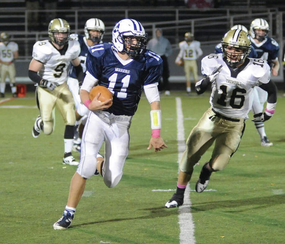 Hour photo/John NashWilton quarterback Brett Phillips runs away from a Trumbull defender during Friday night's game. Phillips ran for more than 300 yards and passed for 90 more, but Trumbull beat the Warriors.
