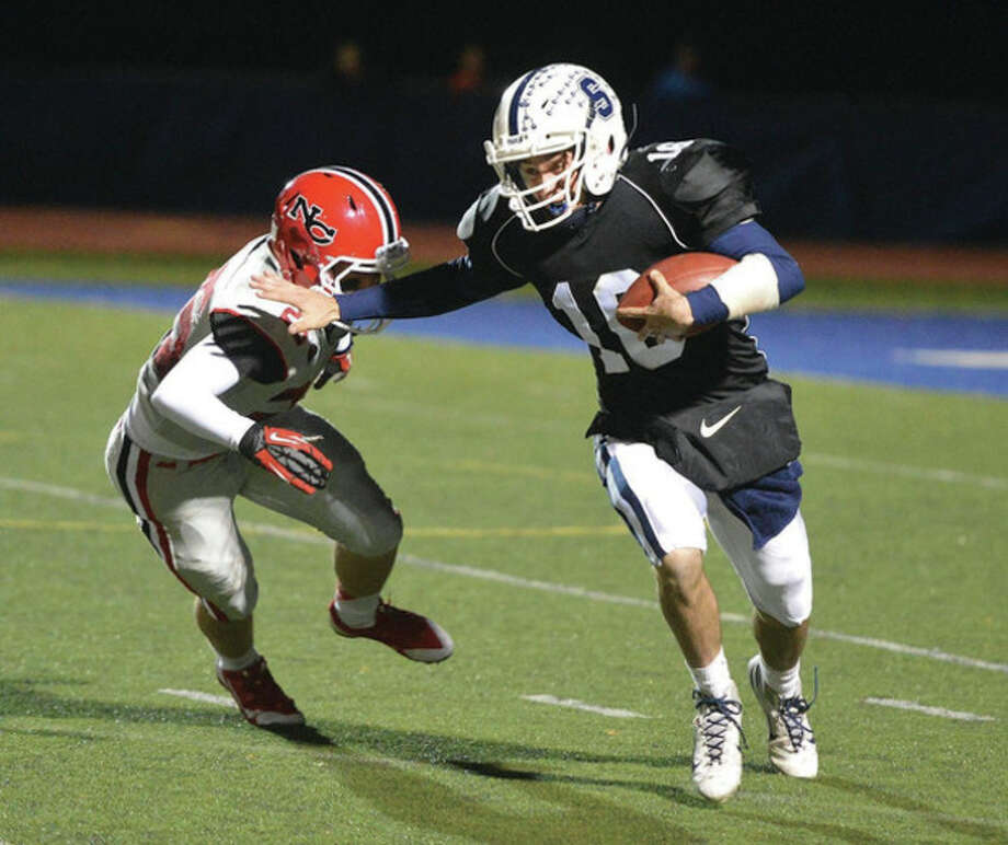 Hour photo/Alex von KleydorffStaples quarterback Jack Massie, right, fends off Cass Knox of New Canaan on a run during Friday night's game in Westport.