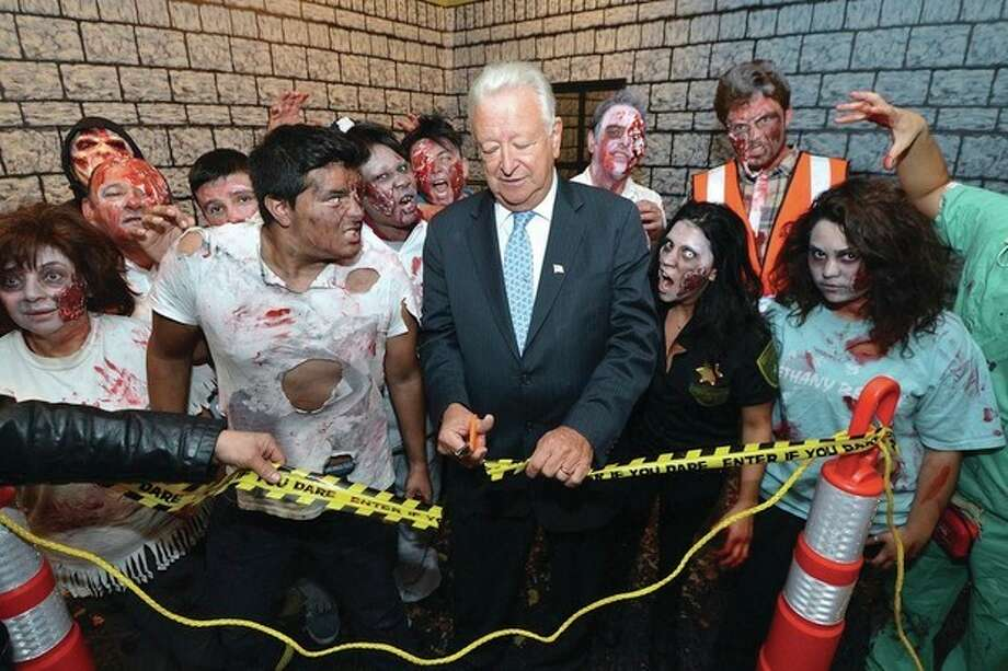 Hour Photo/Alex von Kleydorff. Mayor Richard Moccia cuts the caution tape surrounded by the walking dead for the zombie haunted house at 25 van zant st
