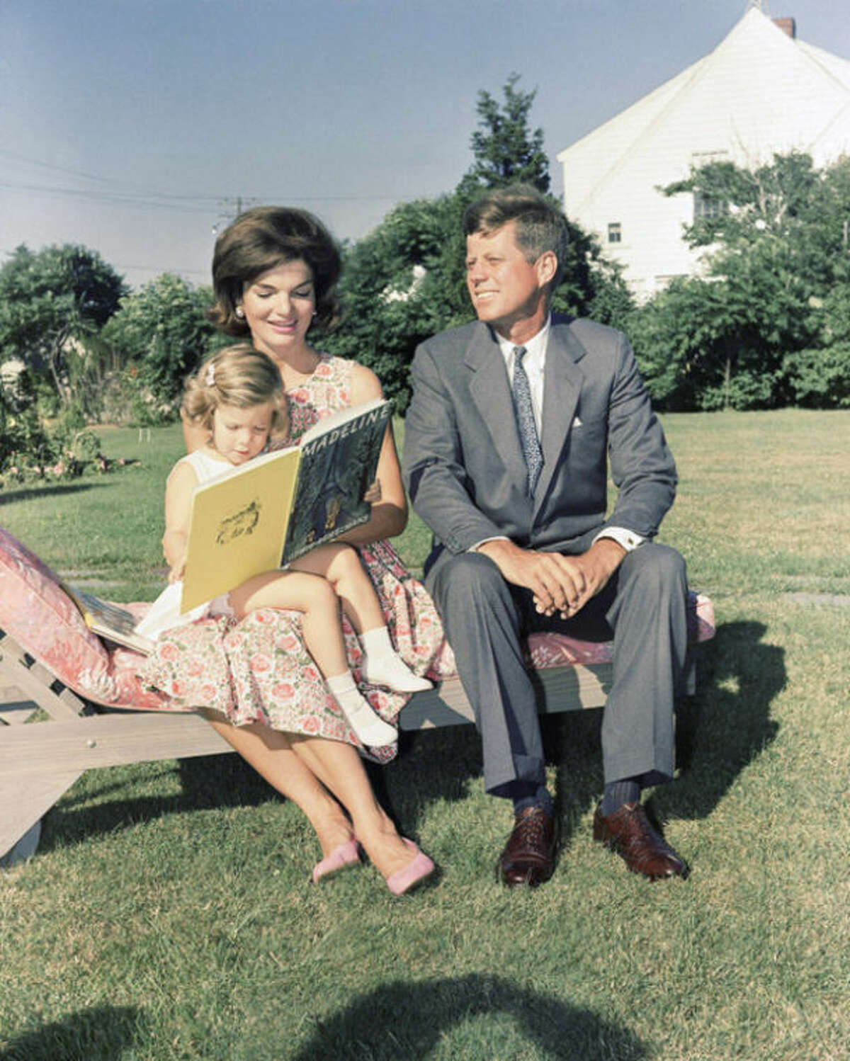 """FILE - In this July 25, 1960 file photo , Sen. John F. Kennedy (D-Mass.) sits with wife, Jacqueline, who reads to their daughter Caroline, at Hyannis Port, Mass. The Kennedy image, the """"mystique"""" that attracts tourists and historians alike, did not begin with his presidency and is in no danger of ending 50 years after his death. Its journey has been uneven, but resilient _ a young and still-evolving politician whose name was sanctified by his assassination, upended by discoveries of womanizing, hidden health problems and political intrigue, and forgiven in numerous polls that place JFK among the most beloved of former presidents. (AP Photo)"""