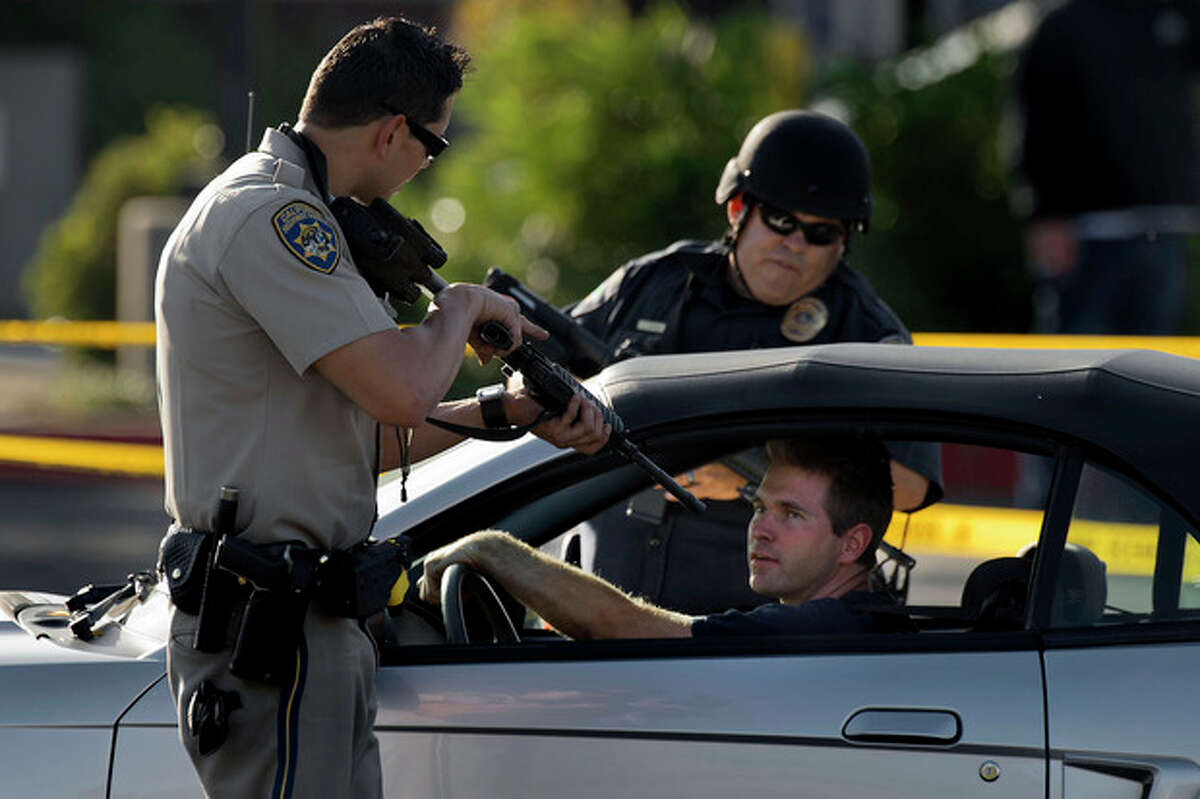 A California Highway Patrol officer and another emergency responder stop a vehicle at a checkpoint near the neighborhood where a federal immigration officer was shot and three local police officers were wounded during a violent confrontation with a suspect in the Sacramento suburb of Roseville on Friday, Oct. 25, 2013. (AP Photo/The Sacramento Bee, Randall Benton)