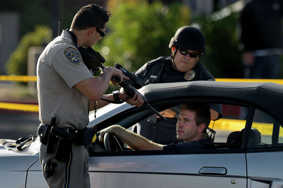 A California Highway Patrol officer and another emergency responder stop a vehicle at a checkpoint near the neighborhood where a federal immigration officer was shot and three local police officers were wounded during a violent confrontation with a suspect in the Sacramento suburb of Roseville on Friday, Oct. 25, 2013. (AP Photo/The Sacramento Bee, Randall Benton) / The Sacramento Bee