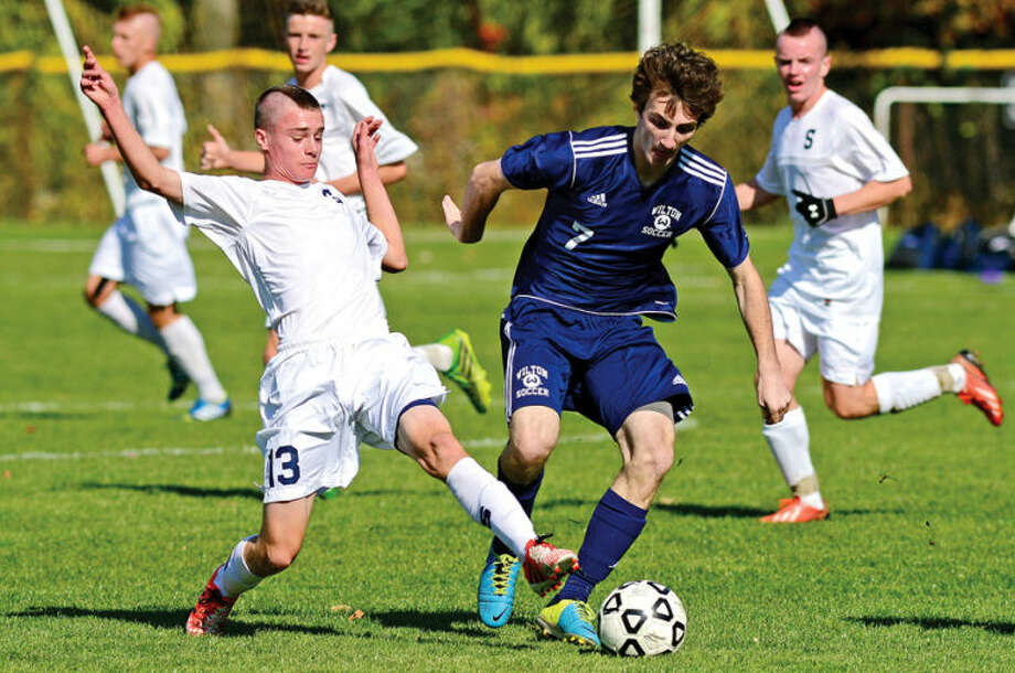 Hour photo / Erik Trautmann Staples #13 Patrick Beusse battles with Wilton's #7 Brendan Devane as the Staples and Wilton boys soccer teams play in their FCIACplayoff game in Westport Saturday.