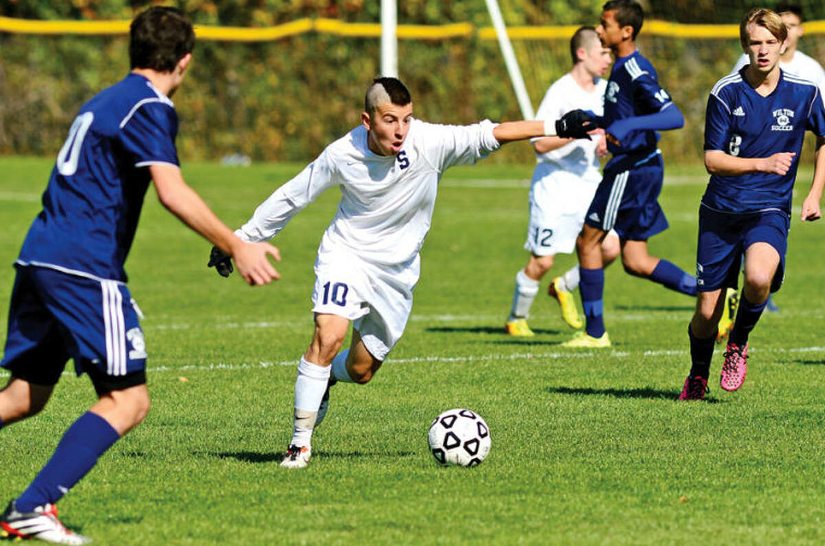 Hour photo / Erik Trautmann Staples #10 Diego Alanis takes a shot on goal as the Staples and Wilton boys soccer teams play in their FCIACplayoff game in Westport Saturday.