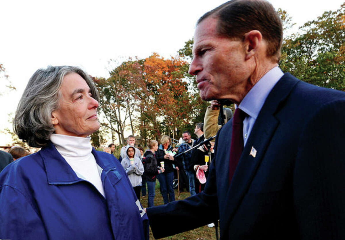 U.S. Sen. Richard Blumenthal gives his support to Maggie Willcox, wife of Capt. Peter Willcox, during a candlelight vigil for him and the crew of Greenpeace's Arctic Sunrise Saturday at Village Creek.