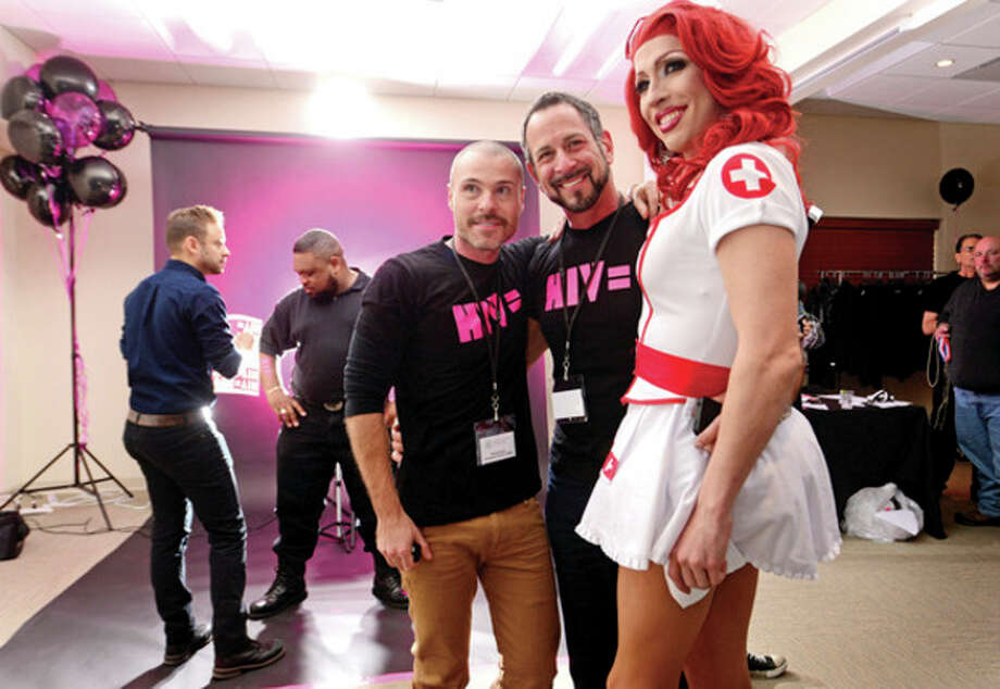 """Hour photo / Erik TrautmannPhotographer Thomas Evans, Dr. Barry Glick and Titania Steele pose for a photo during LGBT Health and Wellness Event on Saturday as World Health Clinicians (WHC) kicked off a new national photo campaign titled """"HIV Equal"""" to help bring about awareness of HIV and HIV testing. / (C)2013, The Hour Newspapers, all rights reserved"""