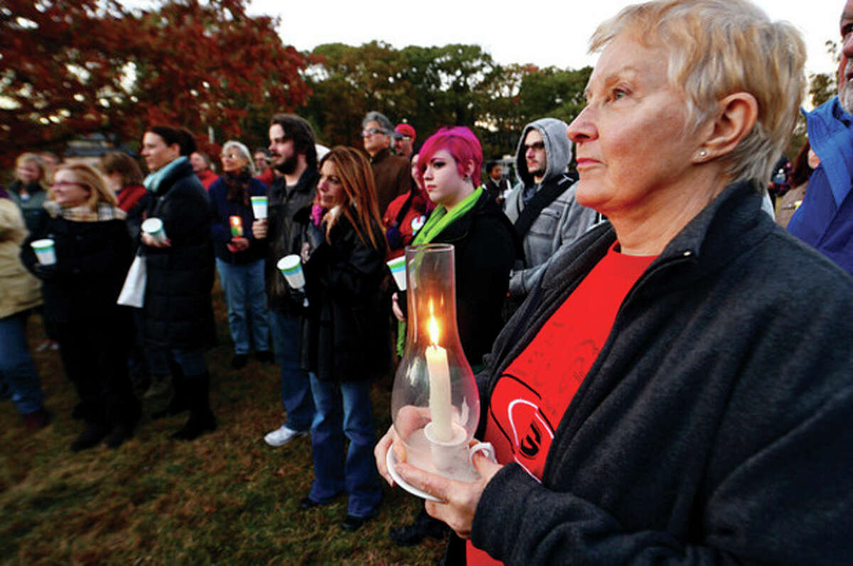 Hour photo / Erik Trautmann Marcia Powell attends a candlelight vigil for Capt. Peter Willcox and the crew of Greenpeace's Arctic Sunrise Saturday at Village Creek.