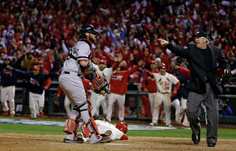 Home plate umpire Dana DeMuthm, right, makes an obstruction call on Boston Red Sox's Will Middlebrooks allowing St. Louis Cardinals' Allen Craig, on ground, to score the game-winning run in the ninth inning of Game 3 of baseball's World Series Saturday, Oct. 26, 2013, in St. Louis. The Cardinals won 5-4 to take a 2-1 lead in the series. Boston Red Sox catcher Jarrod Saltalamacchia watches the call. (AP Photo/Matt Slocum) / AP
