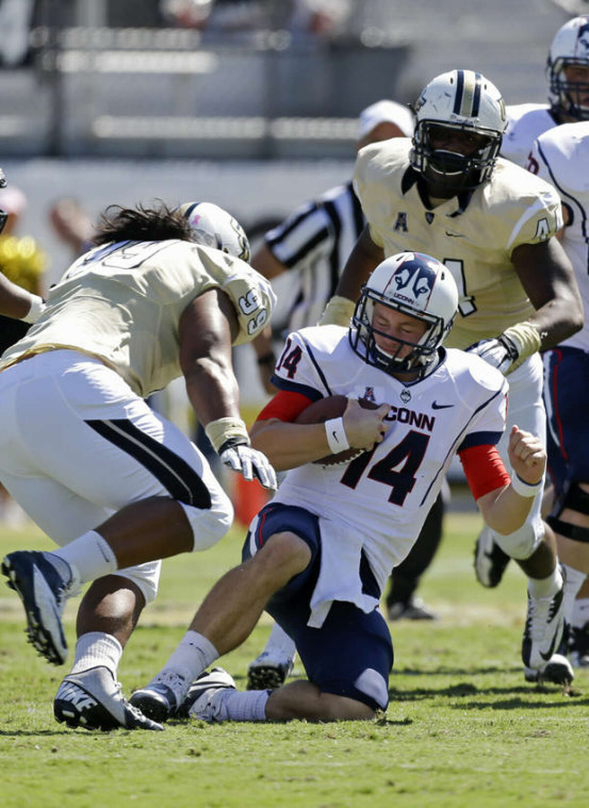 Connecticut quarterback Tim Boyle (14) slides to the turf before his is tackled by Central Florida defensive linemen Jaryl Mamea (99) and Miles Pace (44) during the first half of an NCAA college football game in Orlando, Fla., Saturday, Oct. 26, 2013.(AP Photo/John Raoux)