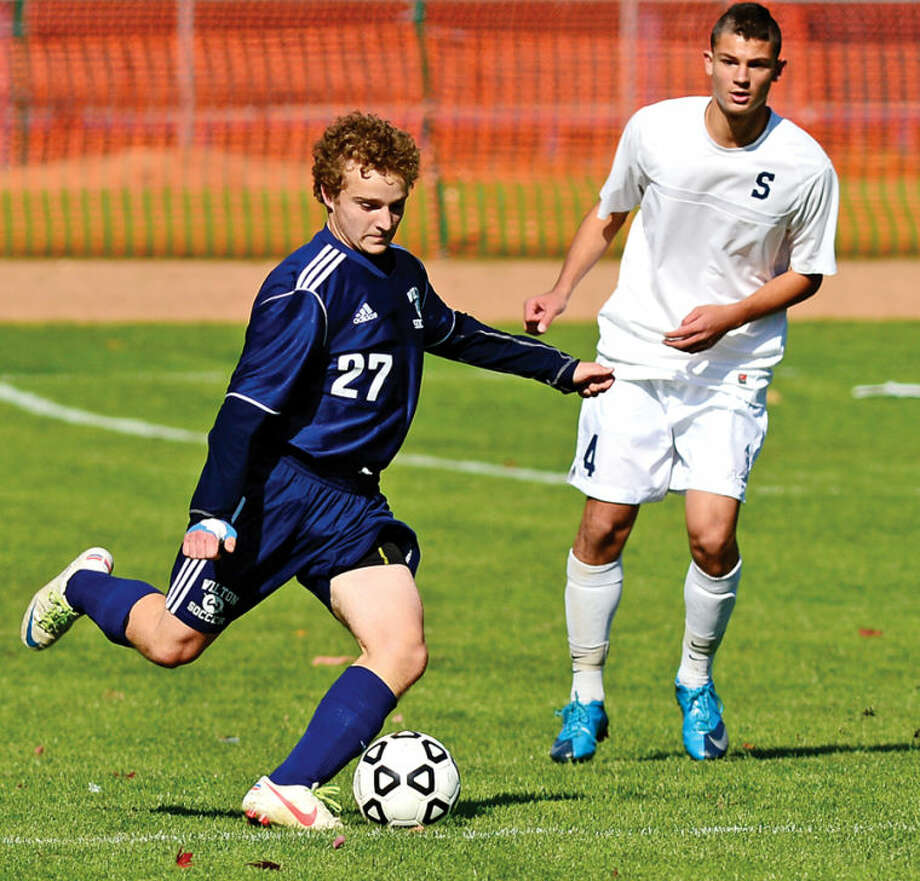 Hour photo / Erik Trautmann Wilton's #27 JOsh Reeve passes the ball as the Staples and Wilton boys soccer teams play in their FCIACplayoff game in Westport Saturday.