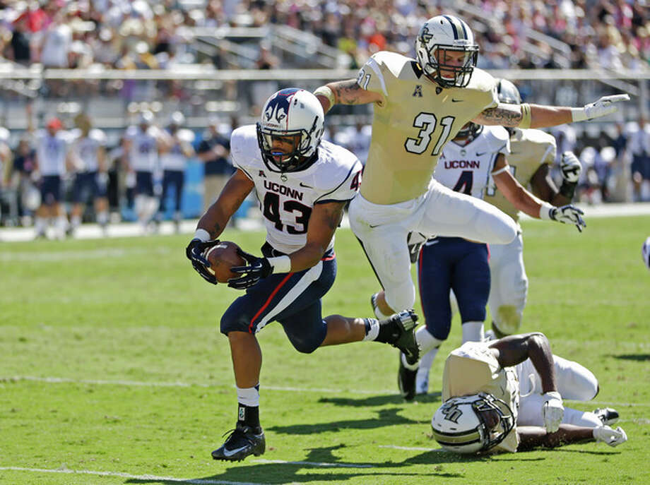 Connecticut running back Lyle McCombs (43) runs past Central Florida defensive backs Sean Maag (31) and Brandon Alexander (37) for a 9-yard touchdown during the first half of an NCAA college football game in Orlando, Fla., Saturday, Oct. 26, 2013.(AP Photo/John Raoux) / AP