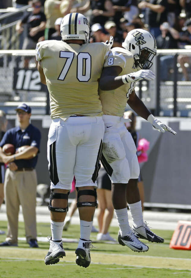 Central Florida running back Storm Johnson (8) celebrate his touchdown against Connecticut on a 7-yard pass play with offensive linesman Chris Martin (70) during the first half of an NCAA college football game in Orlando, Fla., Saturday, Oct. 26, 2013.(AP Photo/John Raoux)