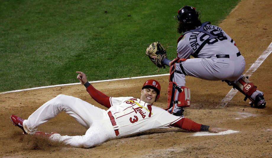 St. Louis Cardinals' Carlos Beltran slides safely past Boston Red Sox catcher Jarrod Saltalamacchia during the seventh inning of Game 3 of baseball's World Series Saturday, Oct. 26, 2013, in St. Louis. Beltran scored from second on a double by Matt Holliday. (AP Photo/David J. Phillip) / AP