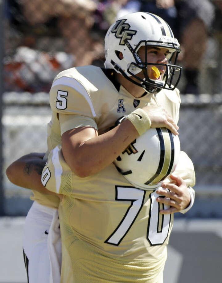Central Florida quarterback Blake Bortles (5) gets a bear hug from teammate offensive linesman Chris Martin (70) after scoring a touchdown on a 10-yard run against Connecticut during the first half of an NCAA college football game in Orlando, Fla., Saturday, Oct. 26, 2013.(AP Photo/John Raoux)