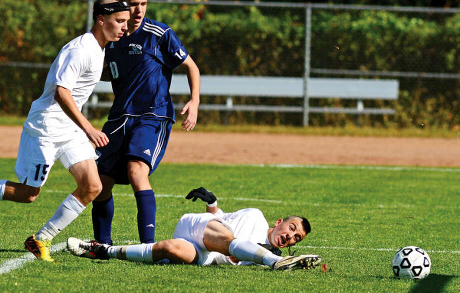 Hour photo / Erik Trautmann Staples #10 Diego Alanis takes a shot on goal from the ground as the Staples and Wilton boys soccer teams play in their FCIACplayoff game in Westport Saturday.