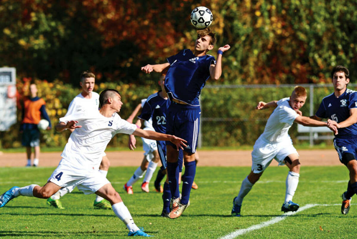 Hour photo / Erik Trautmann Wilton's #3 AJ Galimi gets his head on the ball as the Staples and Wilton boys soccer teams play in their FCIACplayoff game in Westport Saturday.